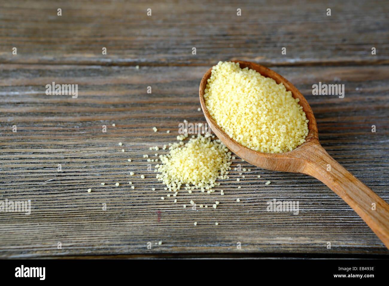 Materias cuscús en una cuchara de madera en las juntas, los alimentos cerrar Imagen De Stock