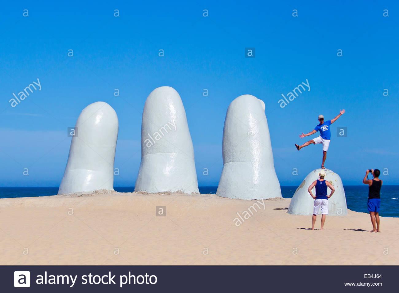 Bañistas y turistas explorando la mano o mano de Punta del Este, creado en 1982 por el artista chileno Mario Imagen De Stock