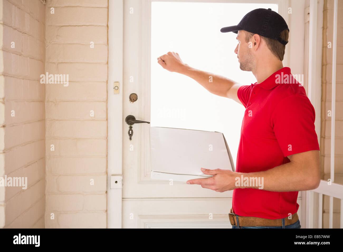 Hombre sujetando entrega pizza mientras llaman a la puerta Foto ...
