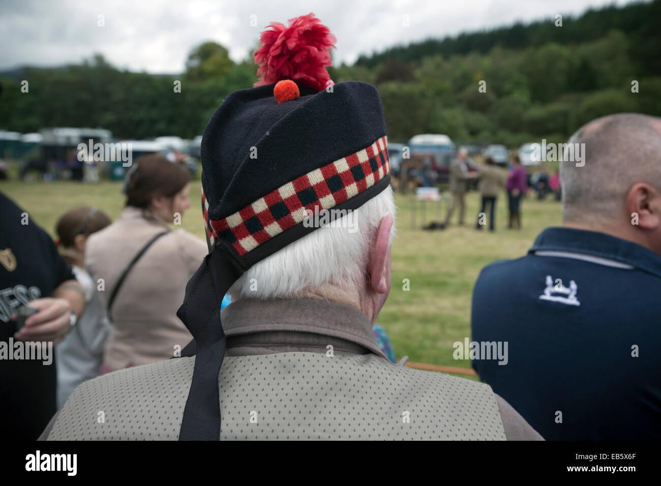 Un hombre que llevaba un sombrero tradicional escocesa Glengarry viendo el  espectáculo en la sociedad agrícola d81c2240123