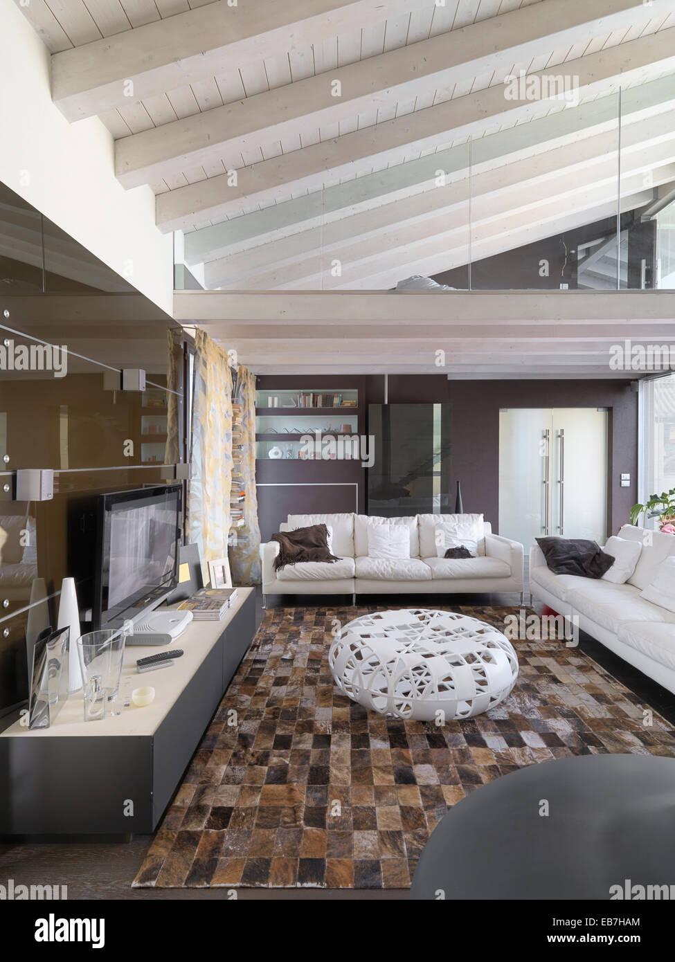 Vista interior de una moderna sala de estar en el ático, con techo de madera y moqueta Imagen De Stock