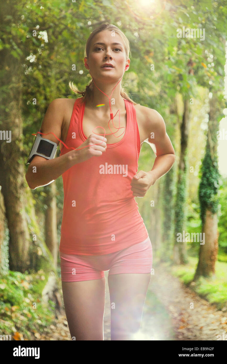 Mujer corriendo en ruta arbolada. Foto de stock