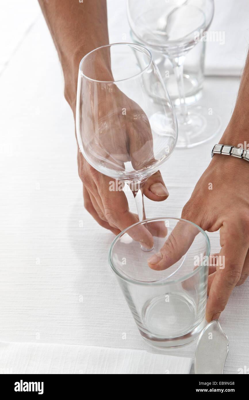 Cerca de las manos del camarero organizar gafas de mesa de restaurante Foto de stock