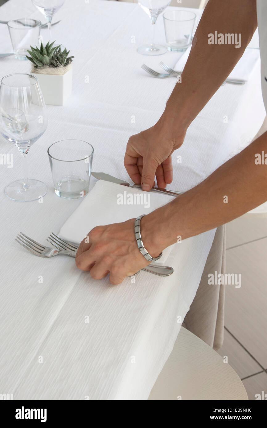 Cerca de las manos del camarero organizar cubiertos de mesa de restaurante Foto de stock