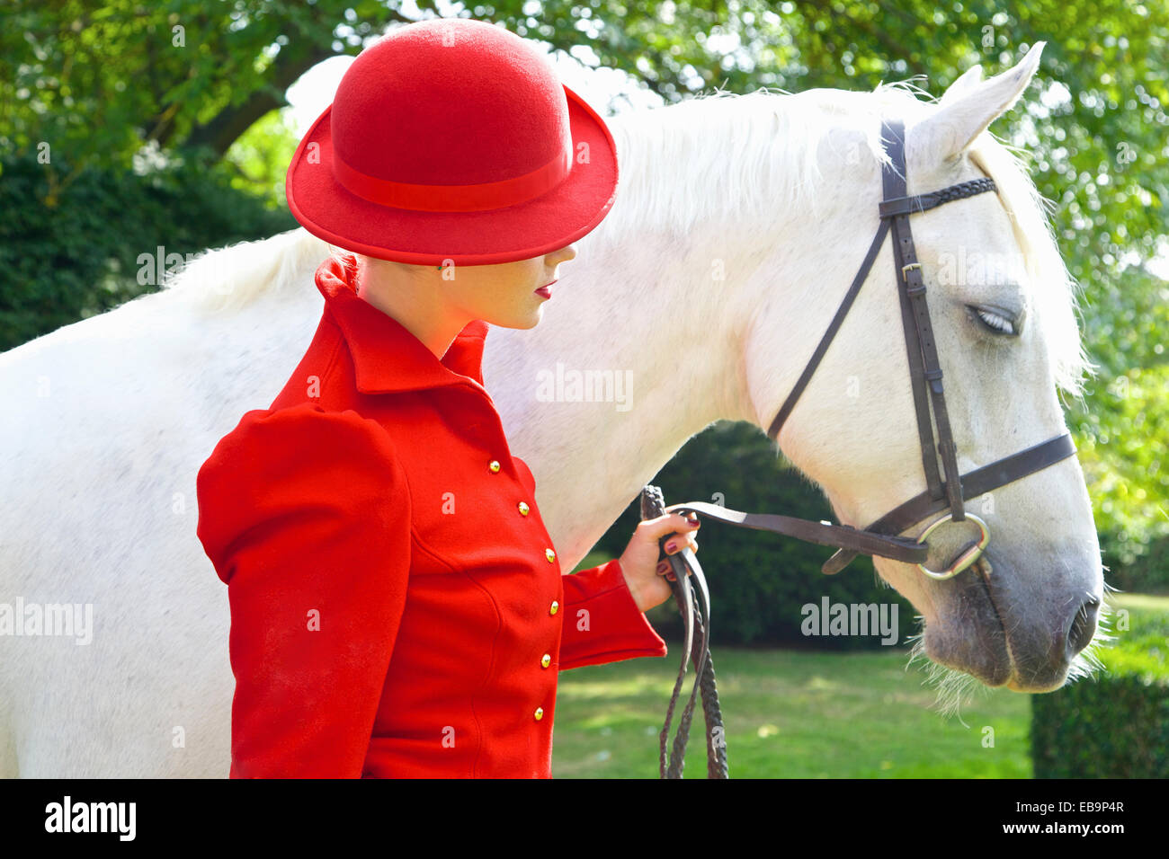 Mujer en rojo traje ecuestre con el caballo Foto de stock