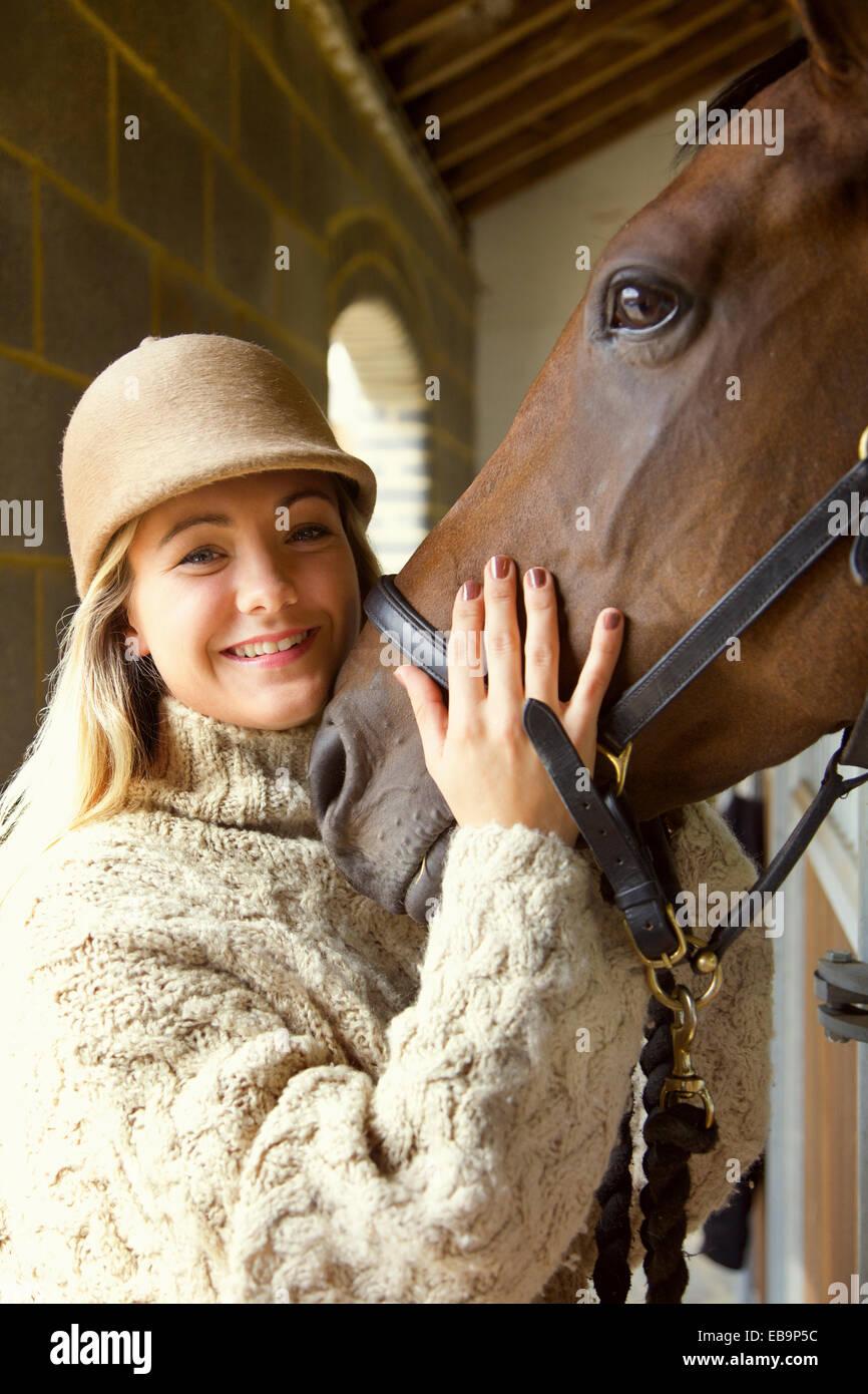 Mujer sonriente acariciando la cabeza del caballo Foto de stock