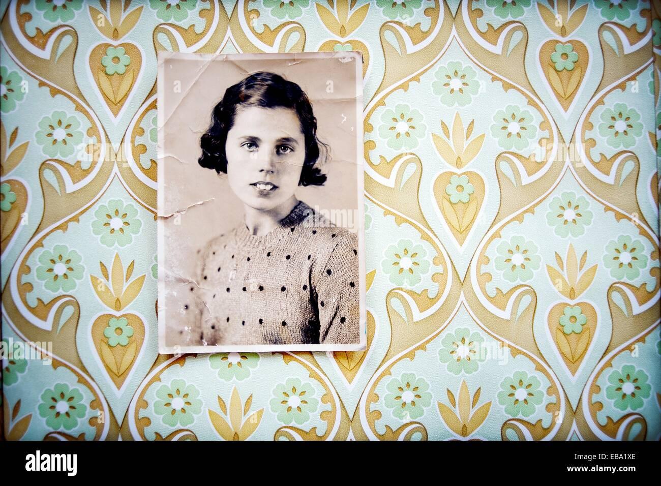 Retrato en blanco y negro de mujer de los años 40 colgada en la pared con papel pintado, vintage, retrato en Imagen De Stock