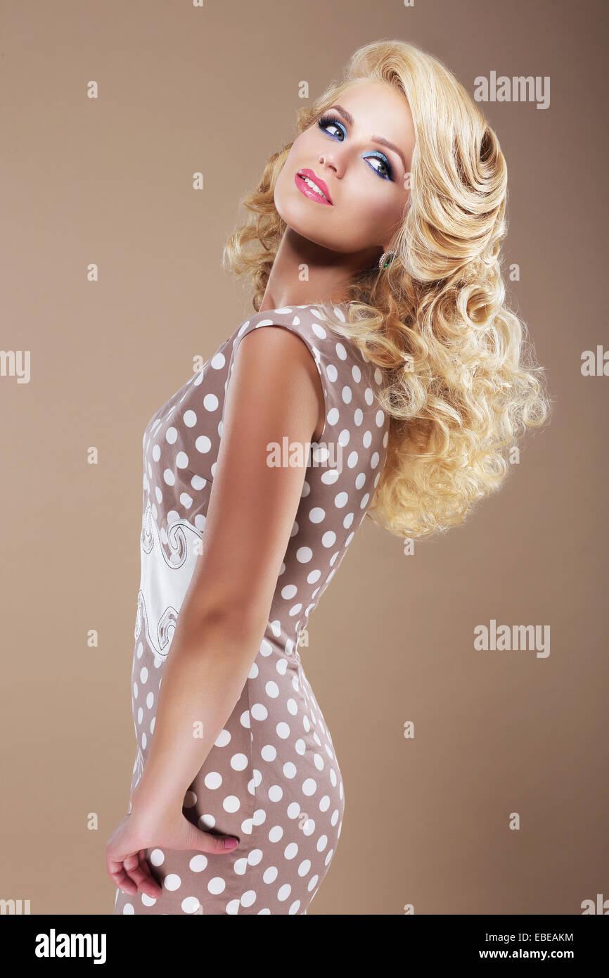 Mujer elegante en traje de lunares Retro mirando atrás Imagen De Stock