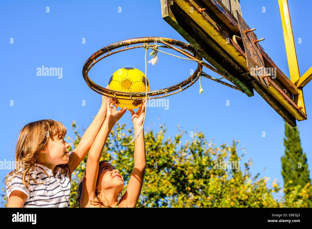 Dos niñas de siete años jugando baloncesto al aire libre Imagen De Stock