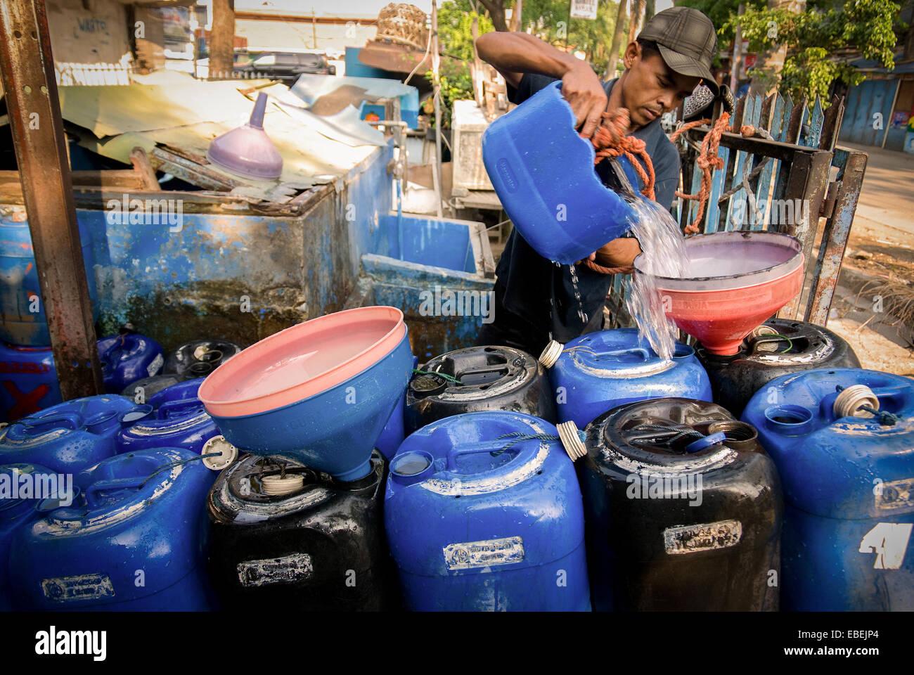 Un hombre llena bidones en el carro con agua de un distribuidor en Tanjung Priok, Yakarta, Indonesia. Imagen De Stock