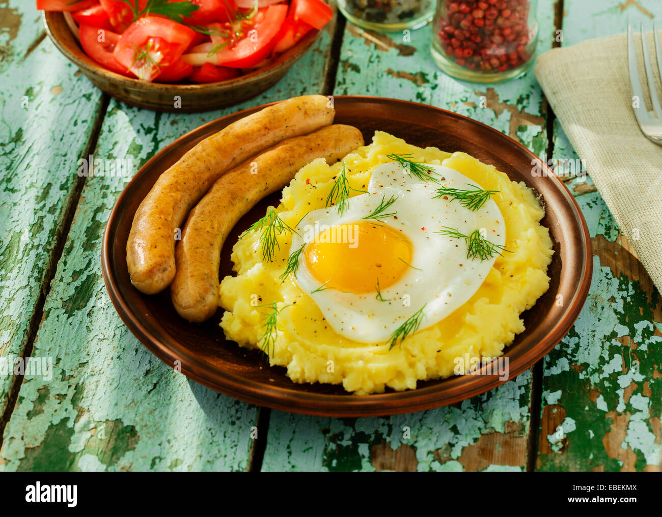 Puré de patatas con huevo frito y salchichas. Imagen De Stock
