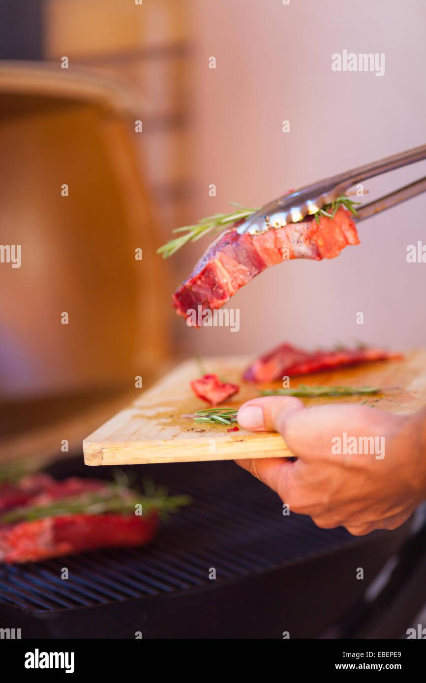 Las manos humanas closeup con bistec de carne fresca preparación en la parrilla Imagen De Stock