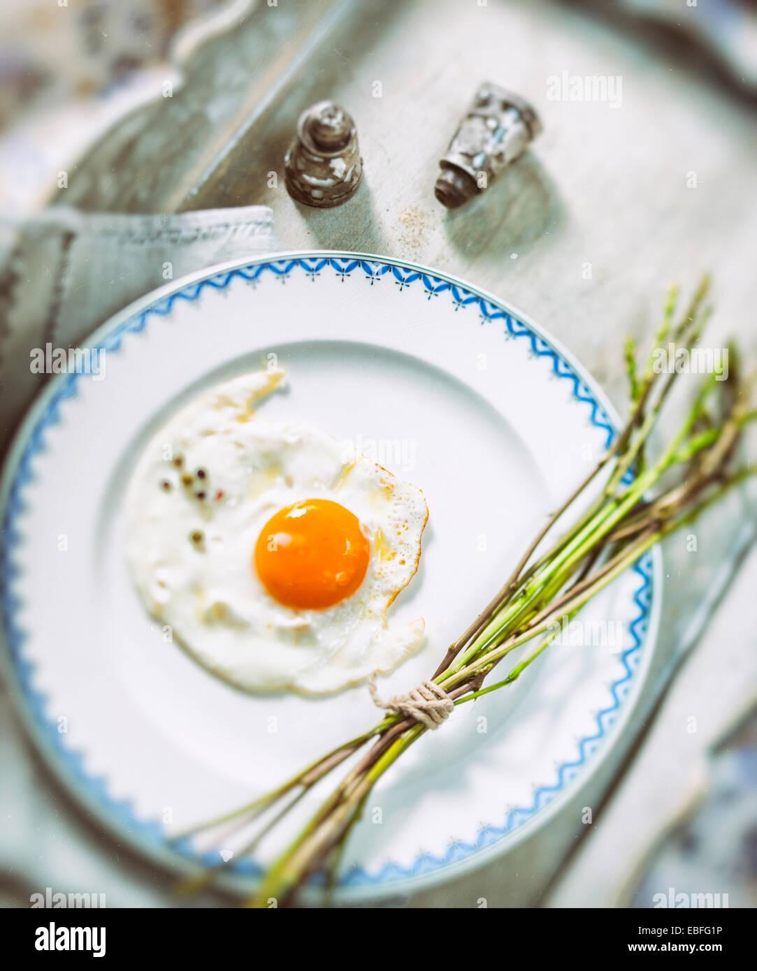Huevo frito y fresca espárragos silvestres en una placa blanca. Imagen De Stock