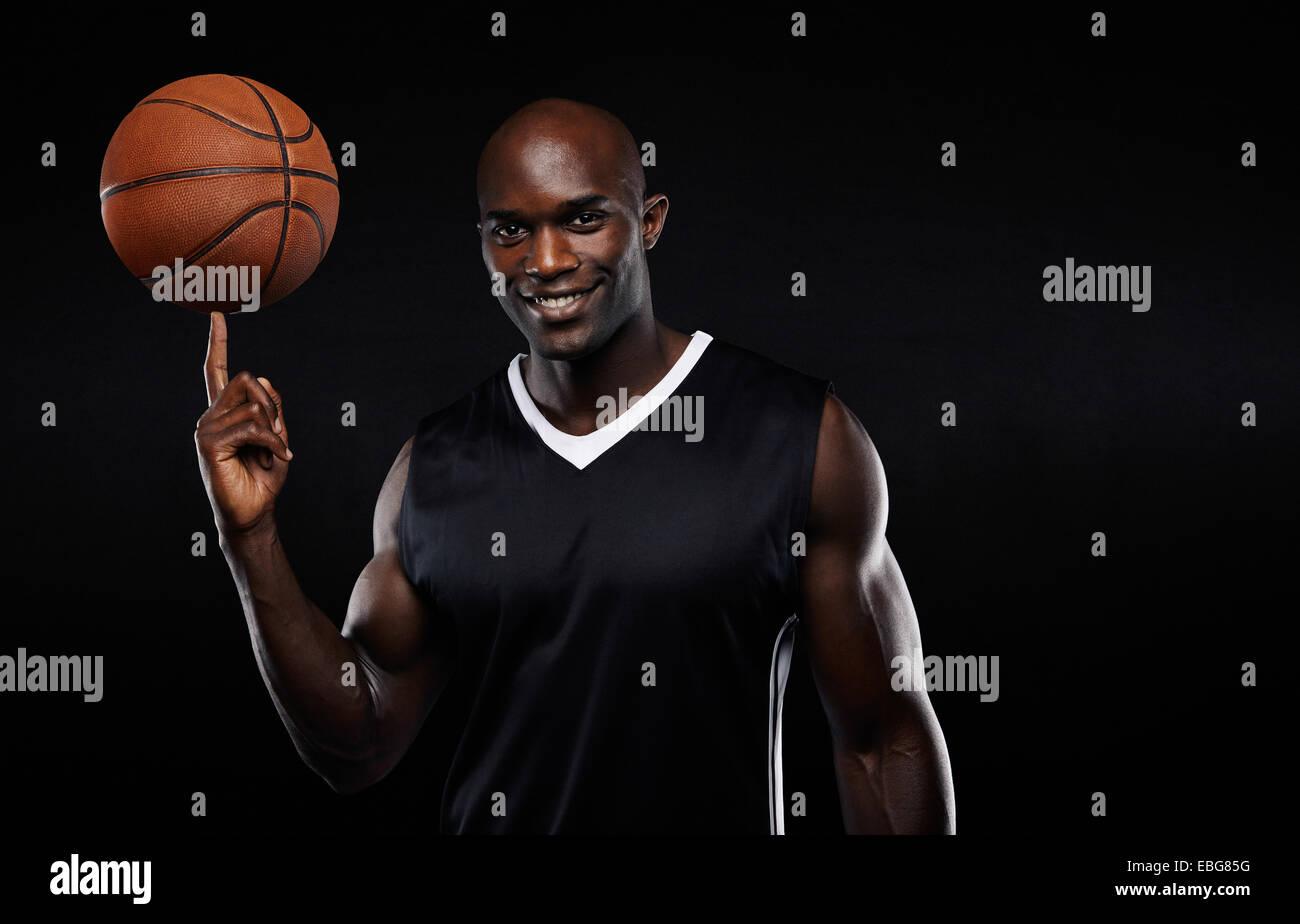 Retrato de feliz joven atleta africano baloncesto equilibrado sobre su dedo. Confía en el jugador de baloncesto Imagen De Stock