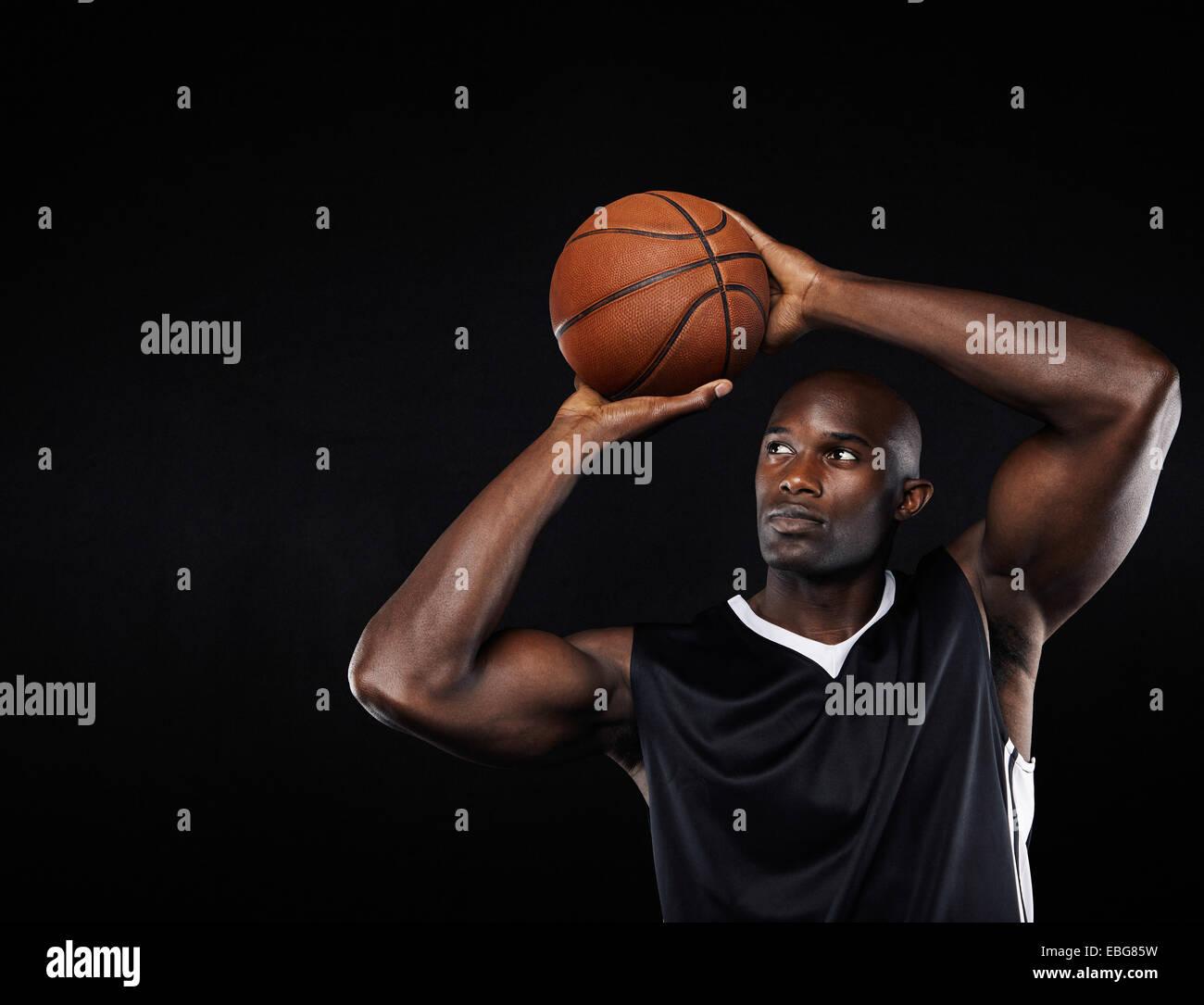 Los jóvenes afroamericanos jugador de baloncesto masculino de disparo en el aro contra fondo negro Imagen De Stock