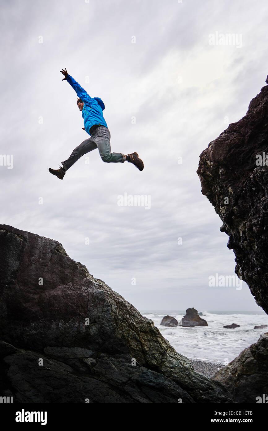 Hombre saltando sobre rocas, Prairie Creek Redwoods State Park, California, EE.UU. Foto de stock