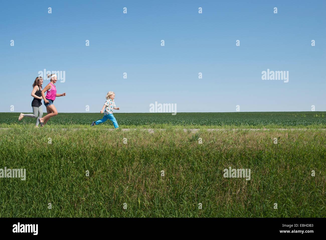 Tres personas corriendo por el campo Imagen De Stock
