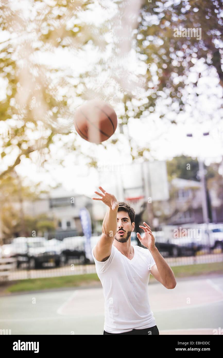 Joven jugador de baloncesto masculino lanzando la bola de baloncesto Imagen De Stock
