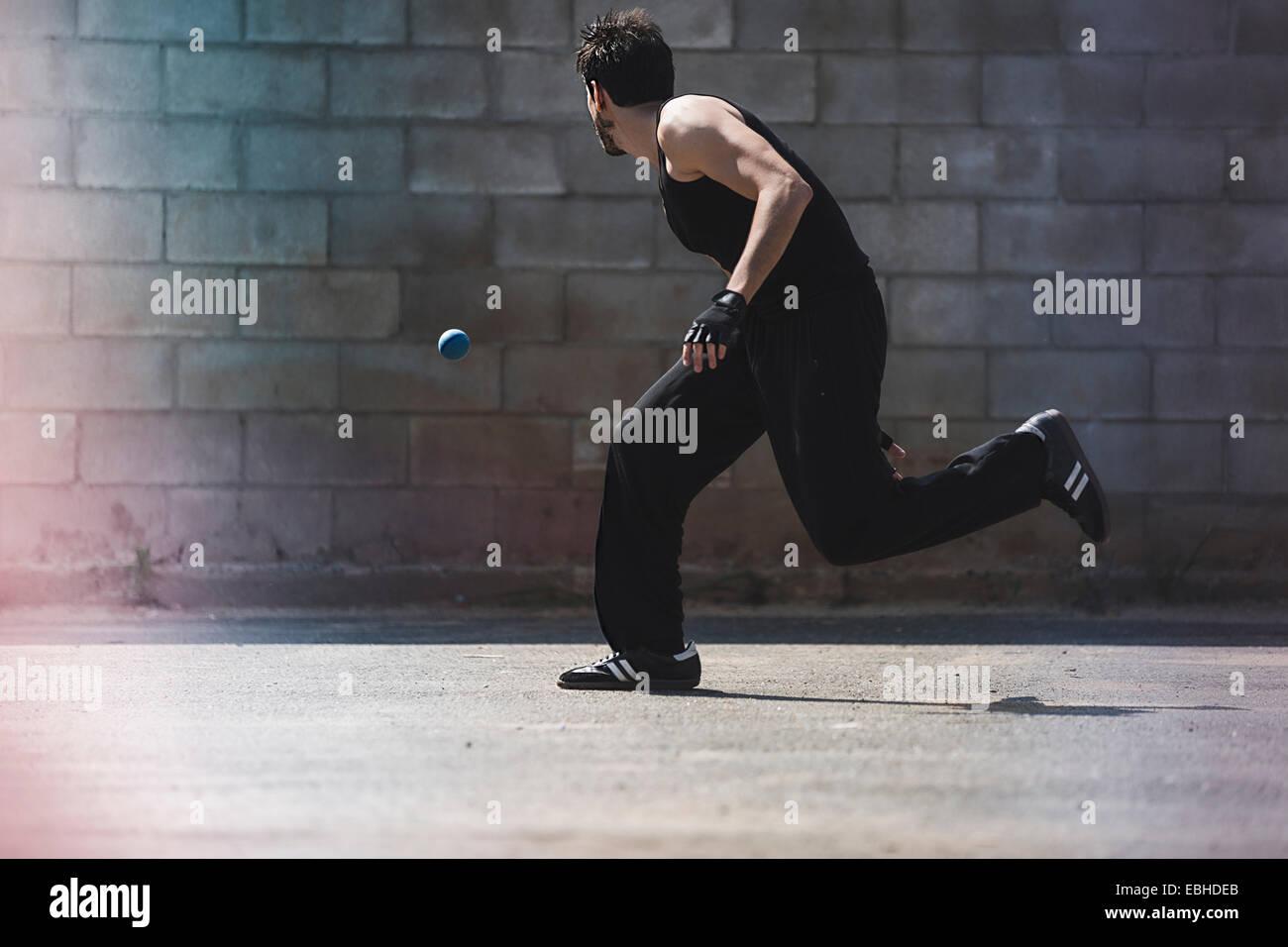 Joven jugador de balonmano masculino ejecutando para pelota Imagen De Stock