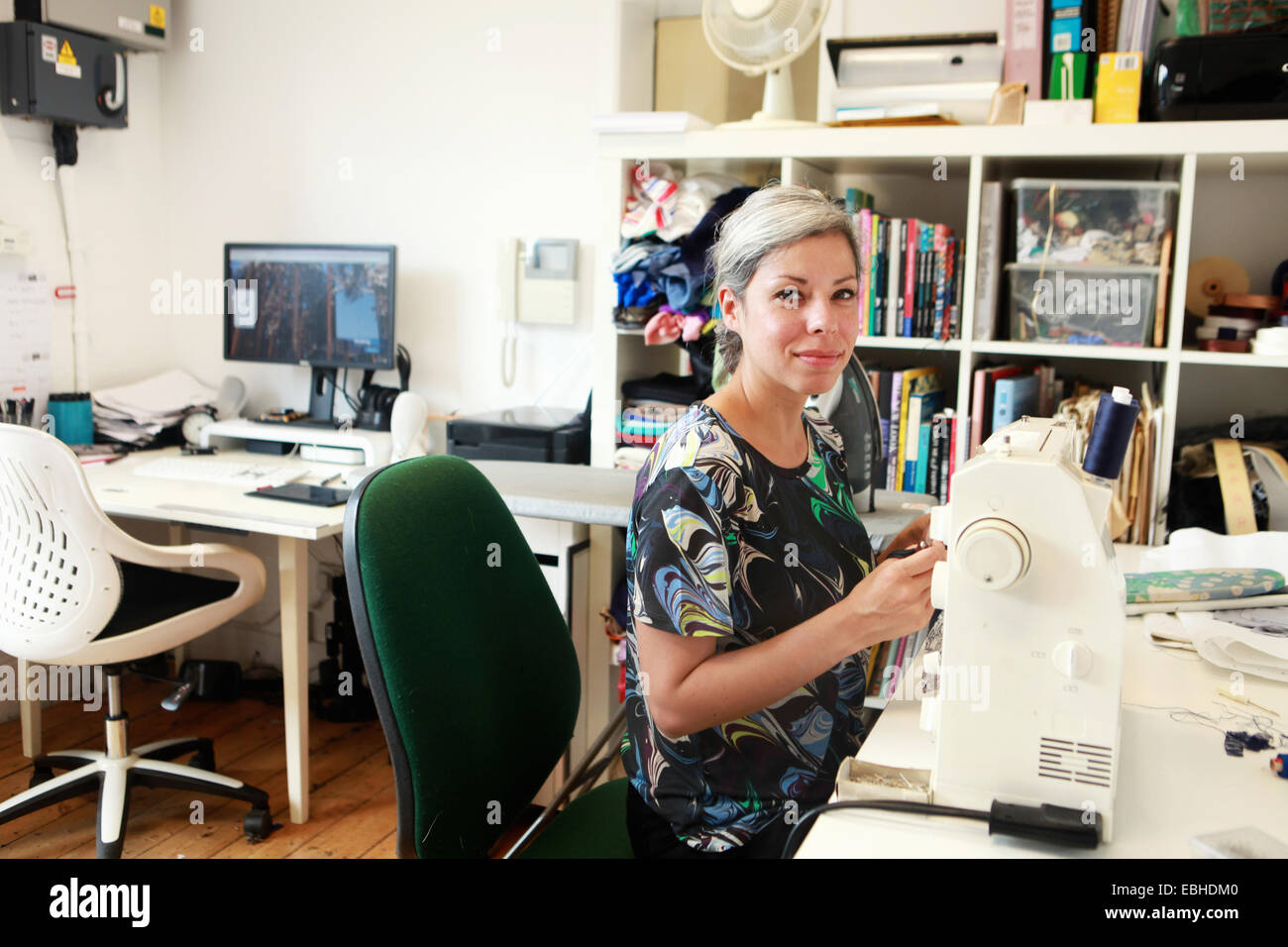 Diseñador que trabaja a máquina de coser en studio Imagen De Stock