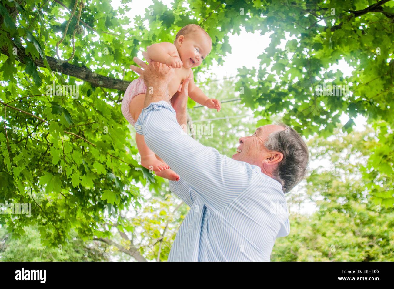 Abuelo levantando bebé nieta en park Imagen De Stock