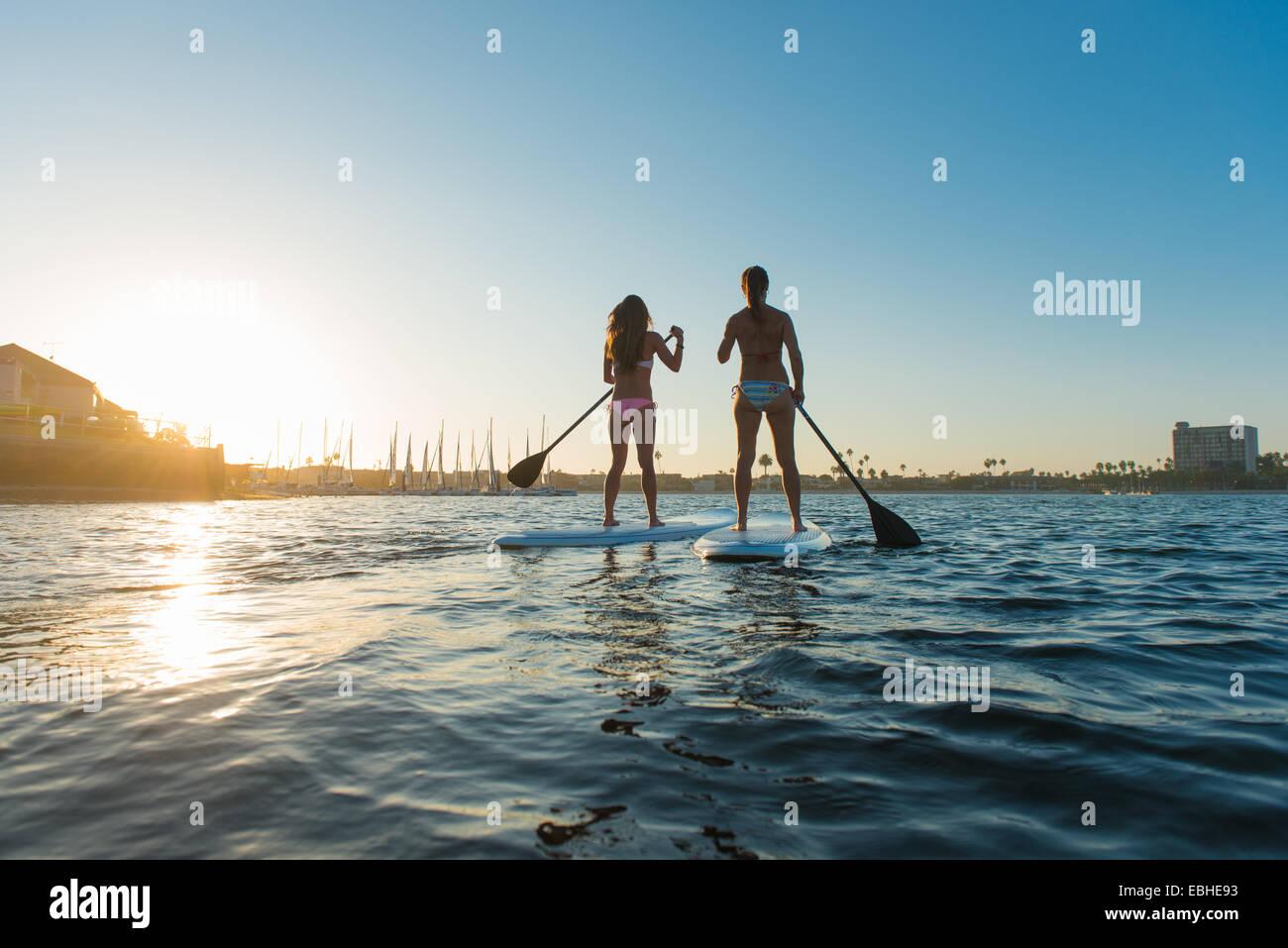 Vista trasera de dos mujeres levántate paddleboarding, Mission Bay, San Diego, California, EE.UU. Imagen De Stock