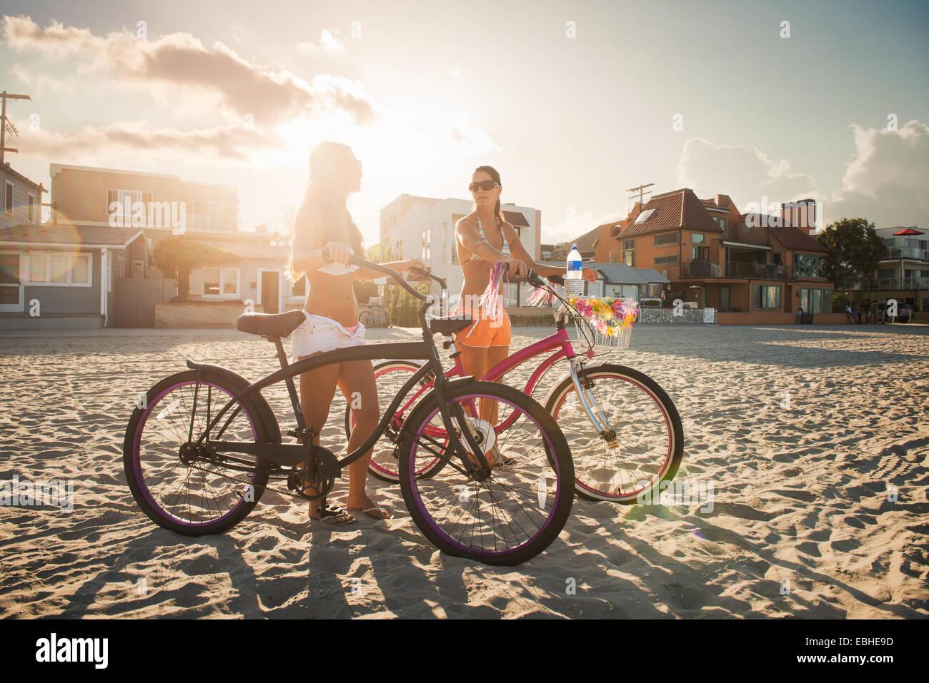 Dos mujeres ciclistas charlando sobre la playa, Mission Bay, San Diego, California, EE.UU. Imagen De Stock