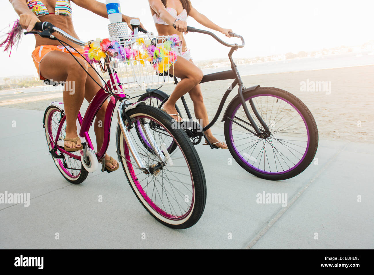 Con el cuello hacia abajo la vista de dos mujeres ciclistas en beach, Mission Bay, San Diego, California, EE.UU. Imagen De Stock