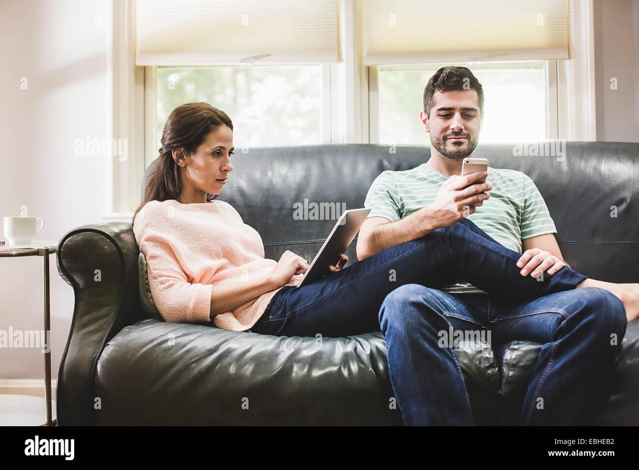 Par utilizando digital tablet y smartphone en el sofá Foto de stock