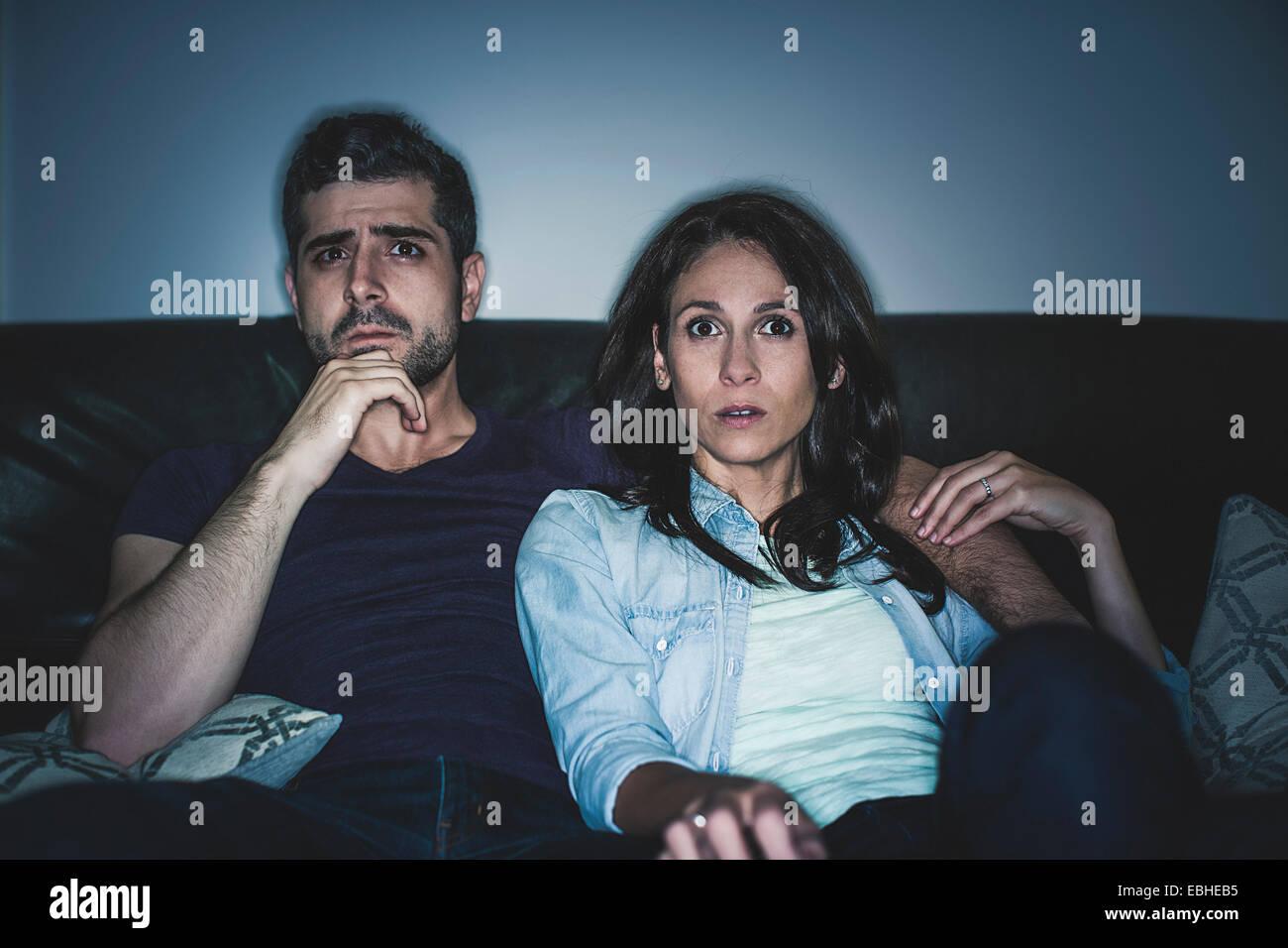 Par ver thriller en el sofá Imagen De Stock