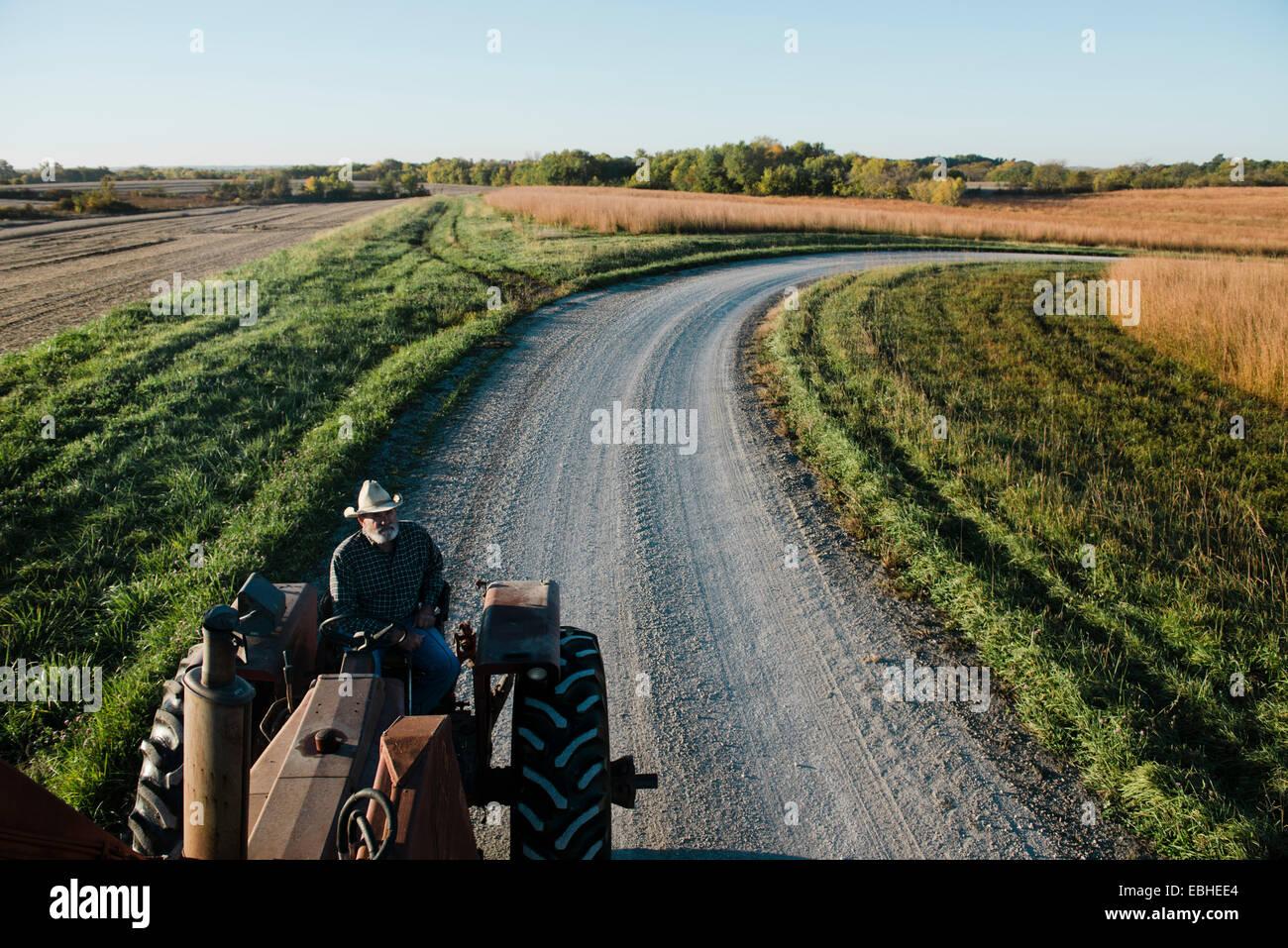Un alto ángulo de visualización de altos agricultor conducción del tractor en carreteras rurales, Imagen De Stock