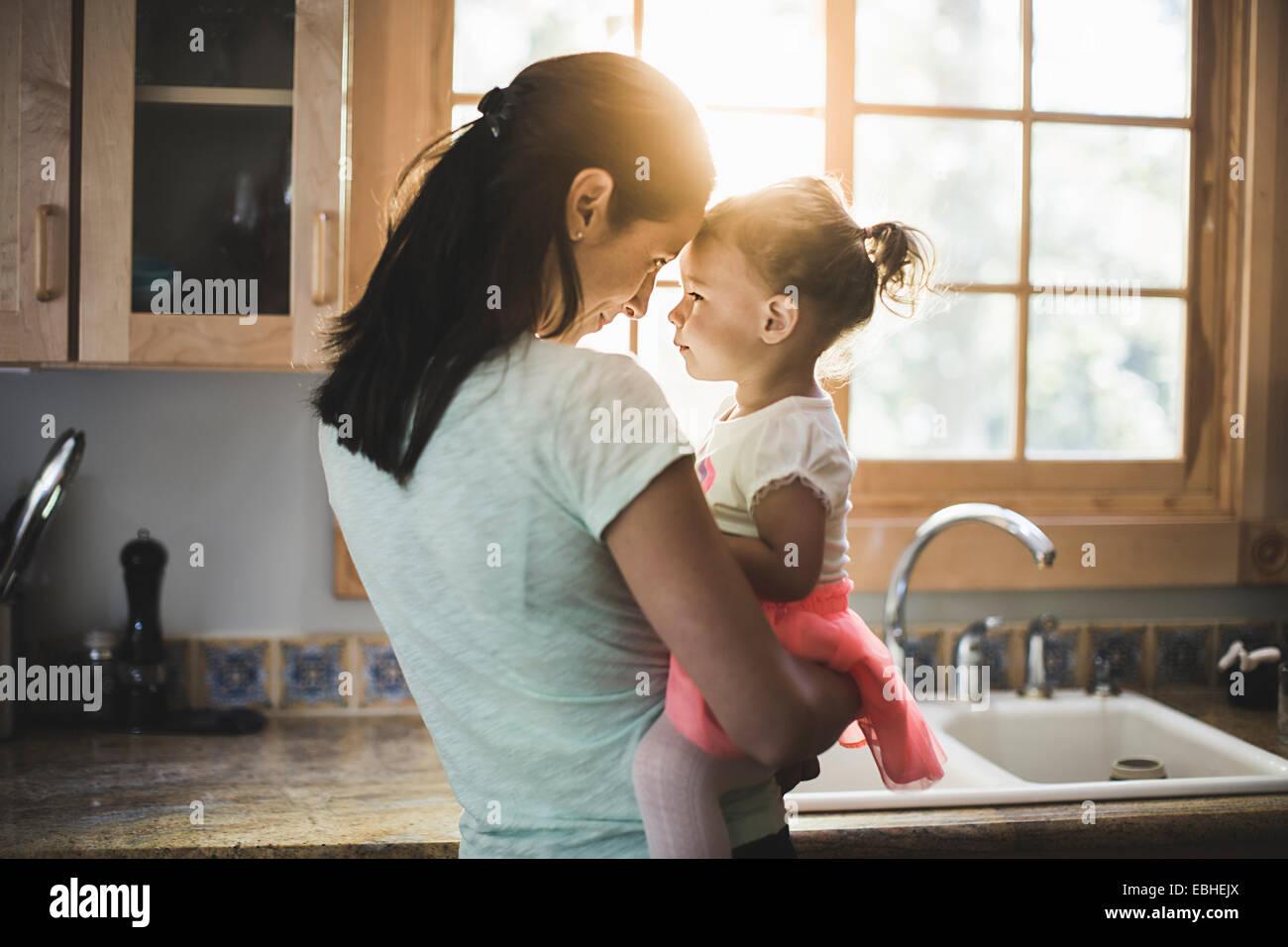 Madre e hija jugando en la cocina Foto de stock