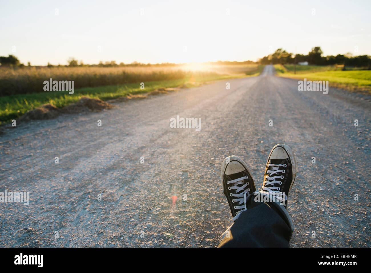 Pies de agricultor viajando por carretera rural al anochecer, Plattsburg, Missouri, EE.UU. Imagen De Stock