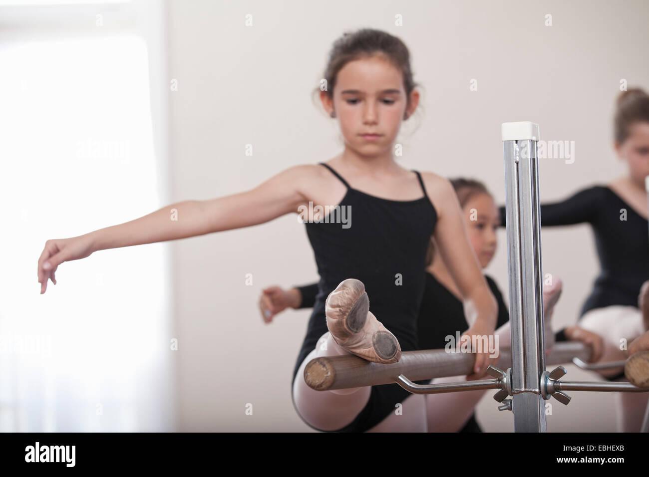 Joven bailarina practicando en barre en ballet school Imagen De Stock