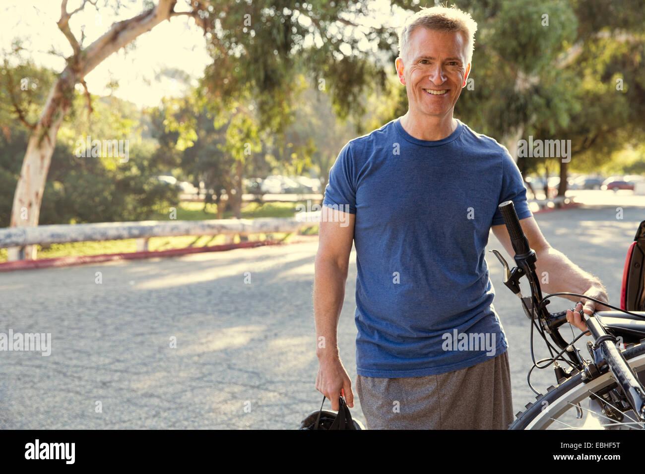 Retrato de macho maduro ciclista en park Imagen De Stock