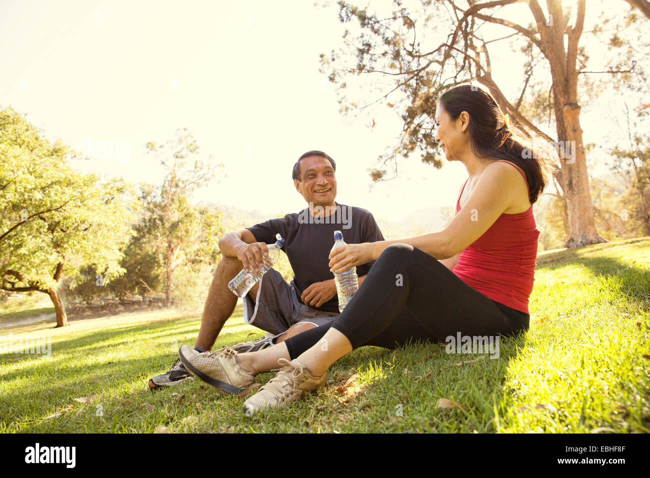 Ejecutando madura pareja tomando un descanso y abastecimiento de agua potable en el parque Imagen De Stock