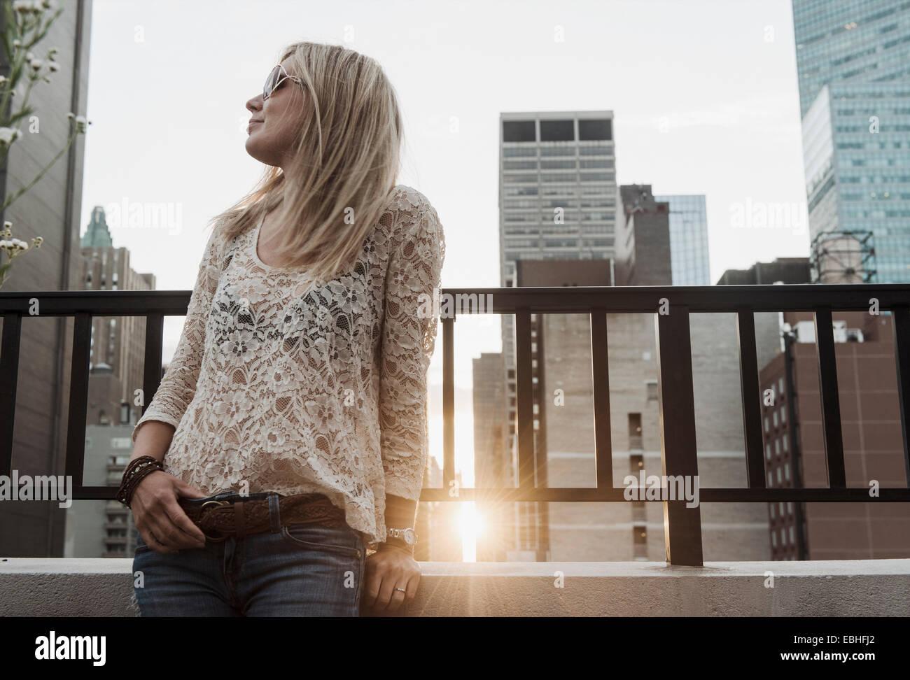Mujer joven en busca de distancia con la ciudad de fondo Imagen De Stock