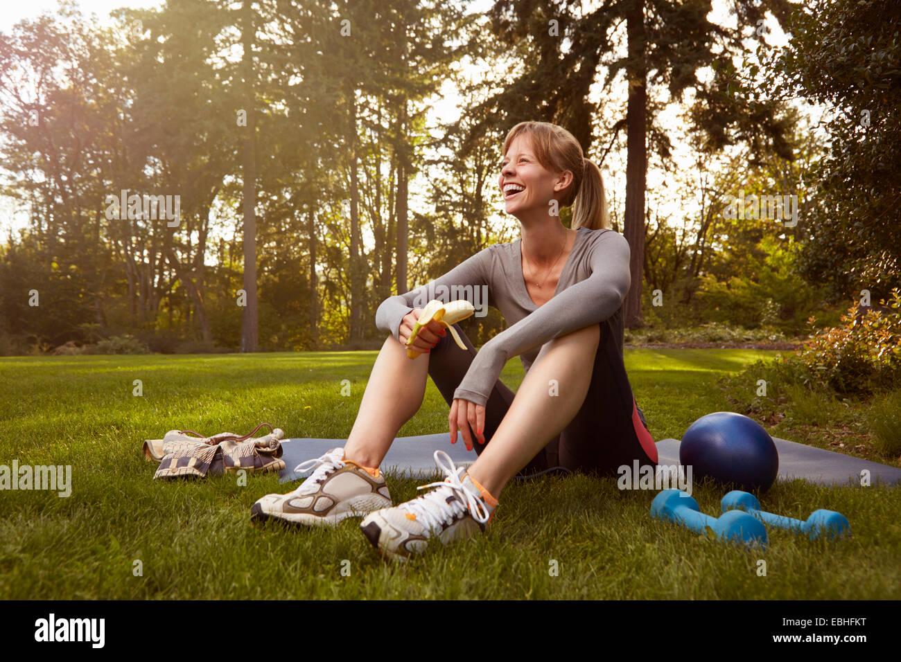 Mujer adulta media sentado en el parque tomando ejercicio romper Imagen De Stock