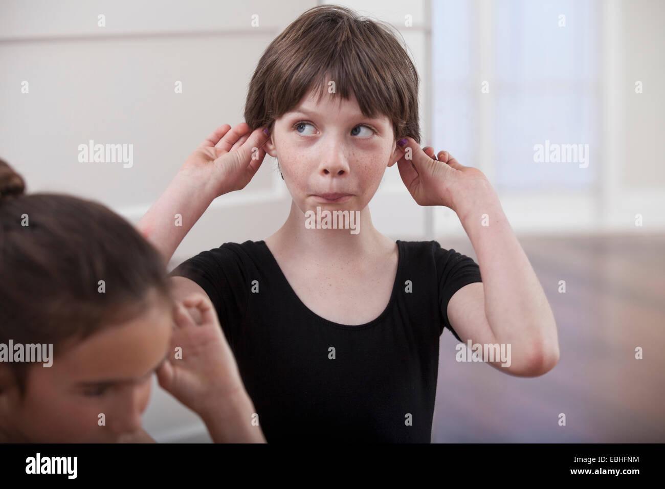 Chica con la celebración de orejas tirando de un rostro en la escuela de ballet Imagen De Stock