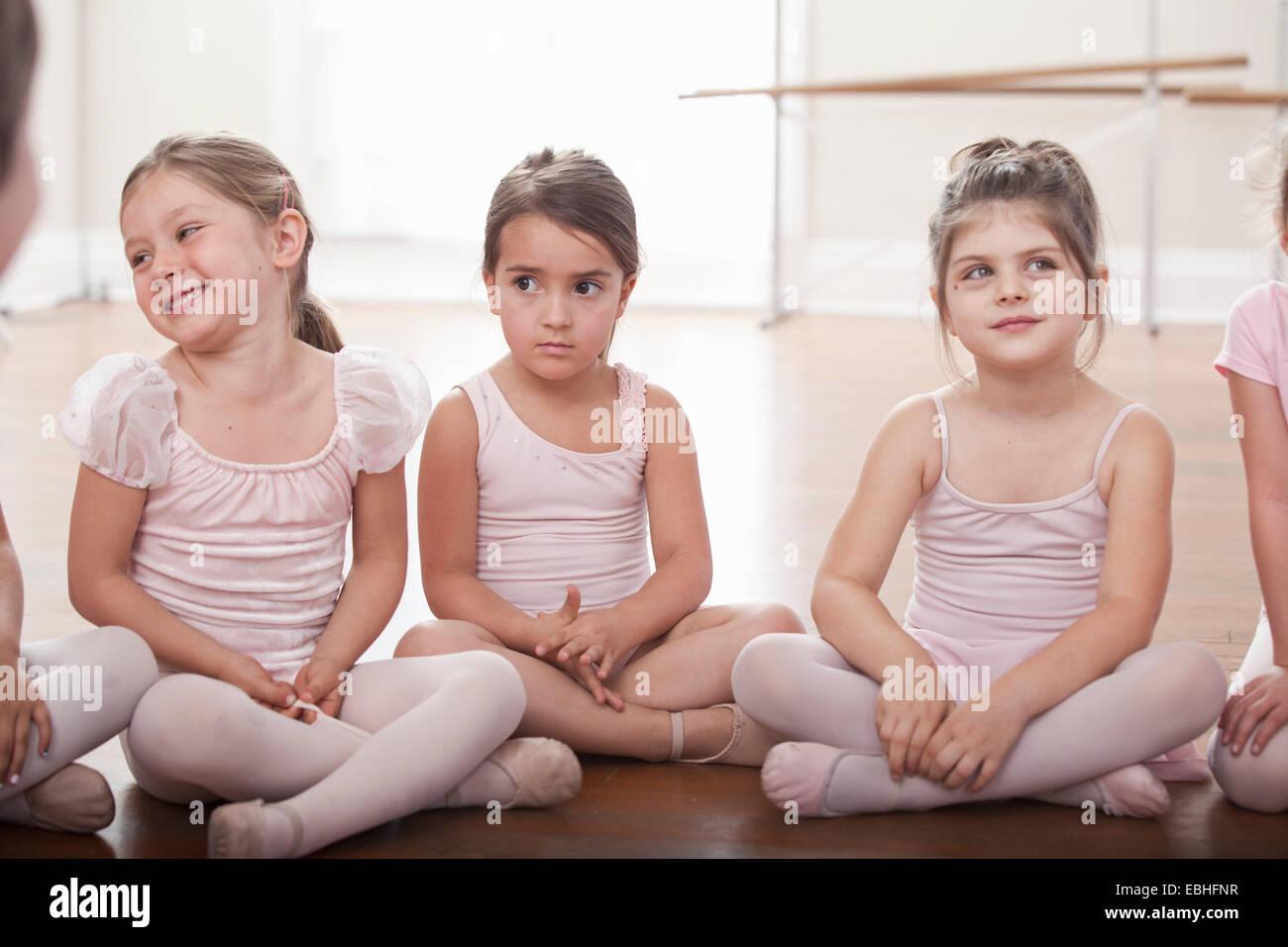 El grupo de niñas sentados en el suelo en la escuela de ballet Foto de stock