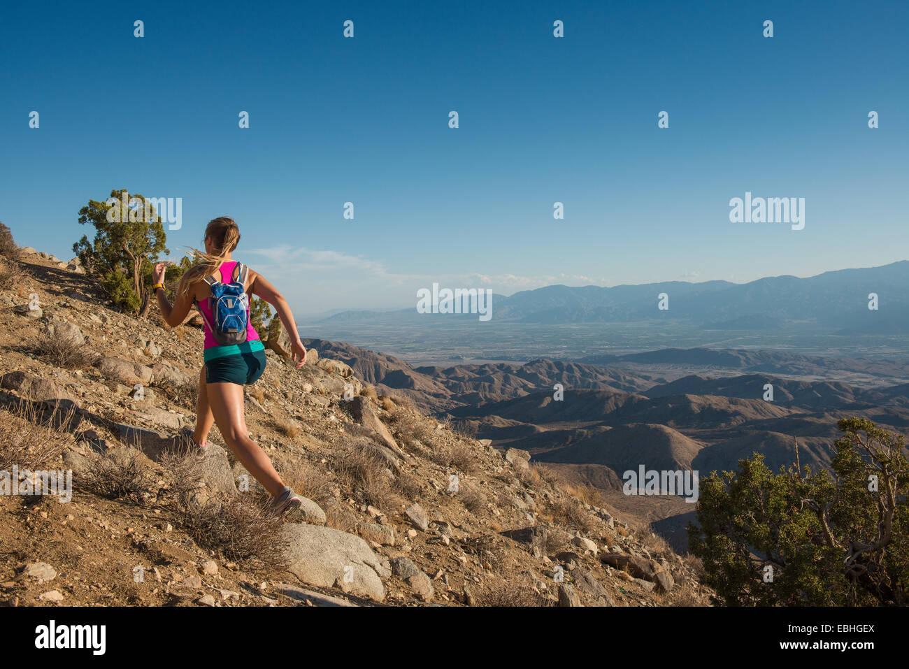 Mujer corriendo en montaña, el Parque Nacional Joshua Tree National Park, California, EE.UU. Imagen De Stock