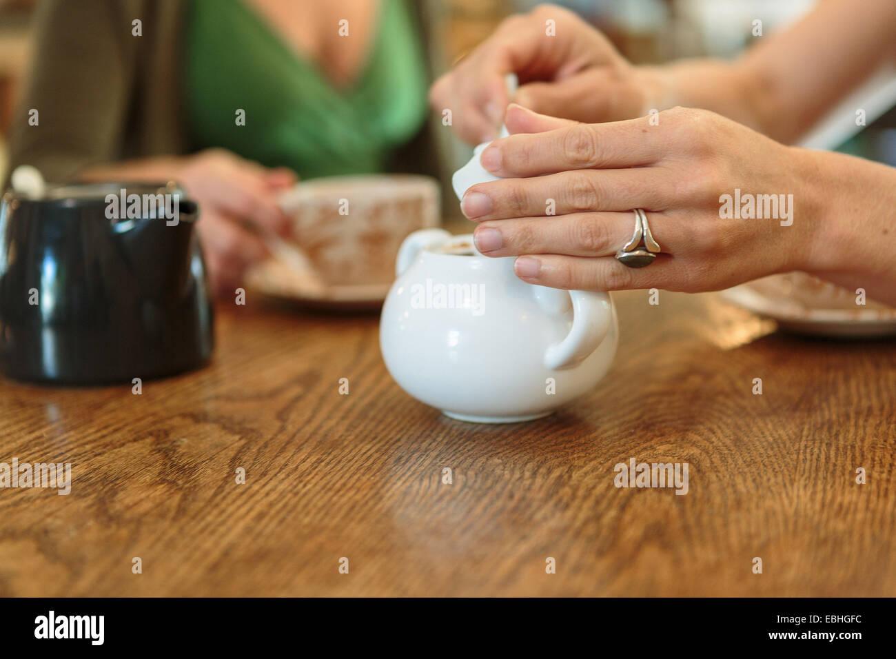 Recorta cerca de dos mediados hembra adulta de manos del tazón de azúcar recogida en Country Store cafe Imagen De Stock