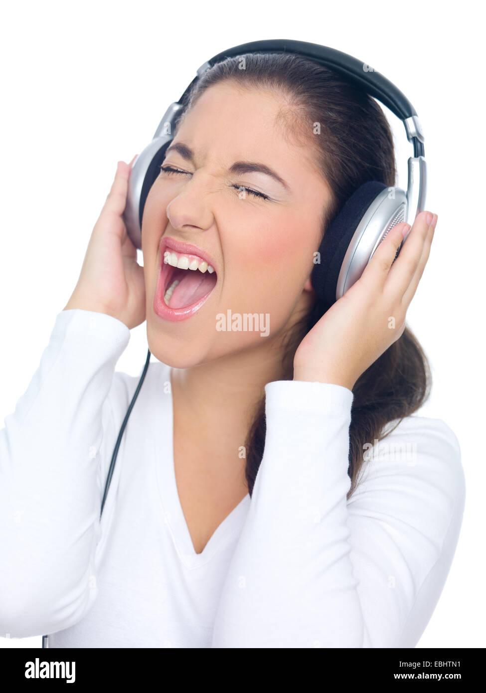 Cerrar feliz Joven en blanco Tops de manga larga cantando ruidosamente subrayando su boca abierta mientras escucha Foto de stock