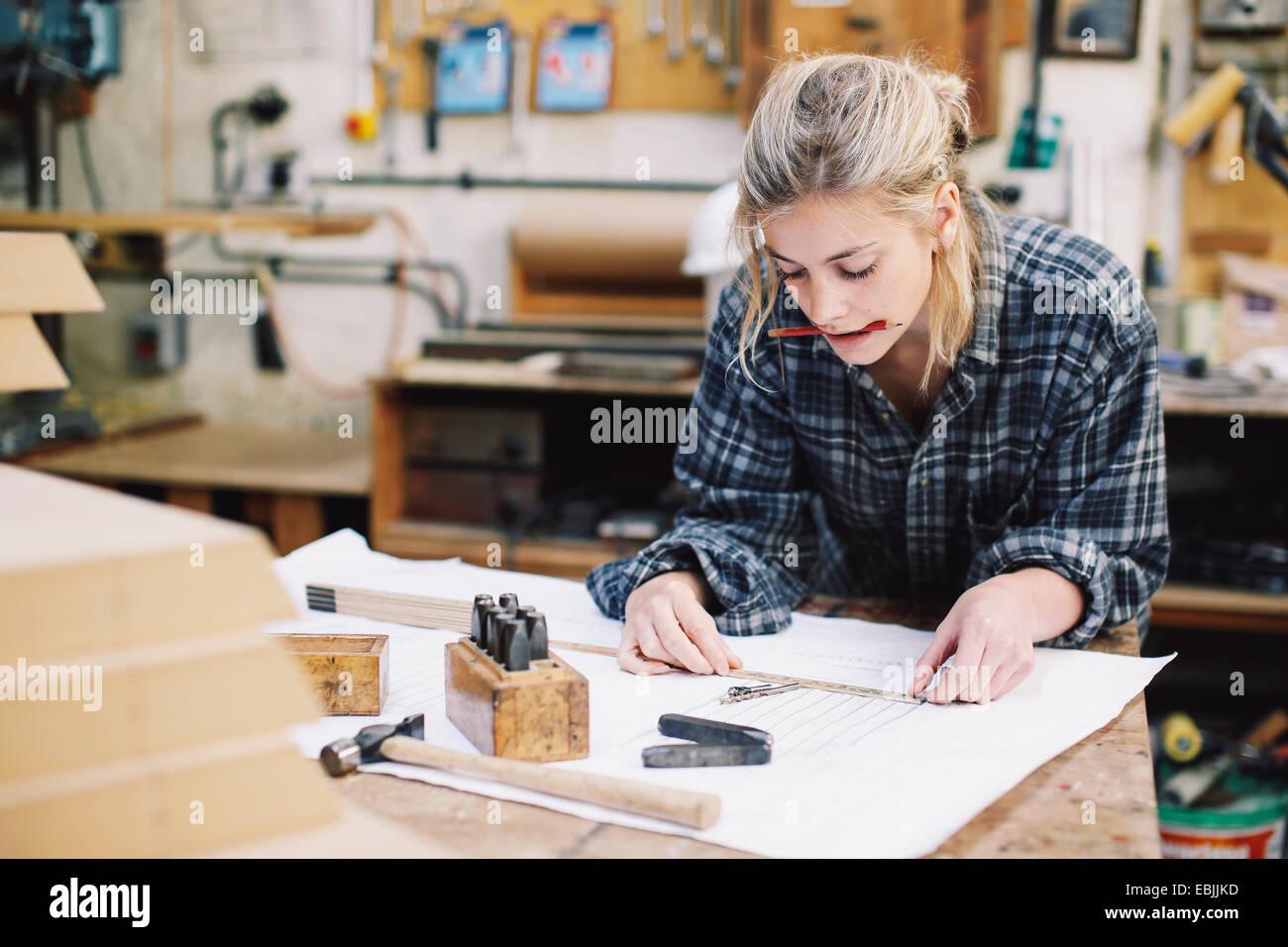 Joven artesana blueprint de medición sobre un banco de trabajo en el taller de órgano de tubos Imagen De Stock
