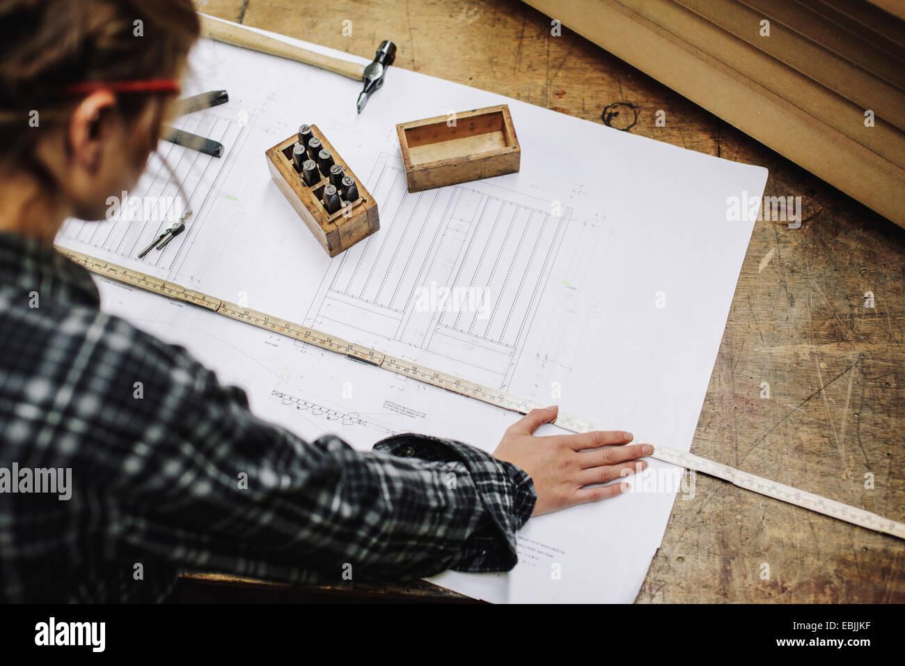 Joven artesana blueprint de medición en taller de órgano de tubos Foto de stock