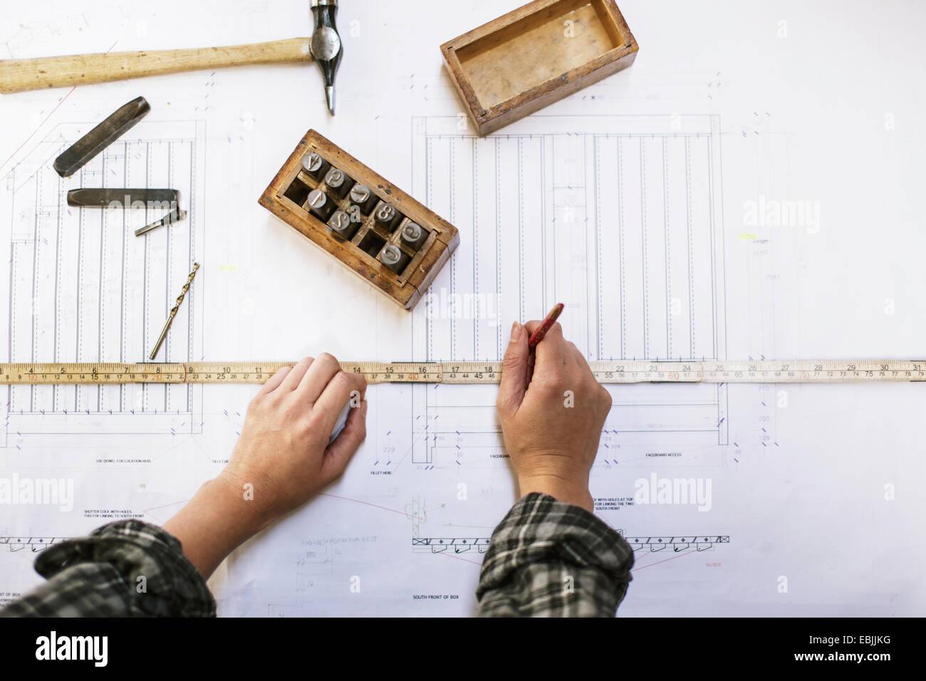 Las manos del joven artesana blueprint de medición en taller de órgano de tubos Imagen De Stock