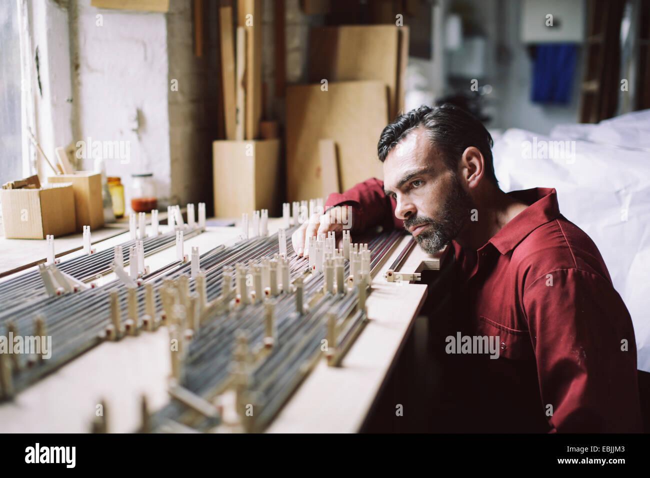 Artesano maduro comprobación de órgano de tubos en pipe organ taller Imagen De Stock