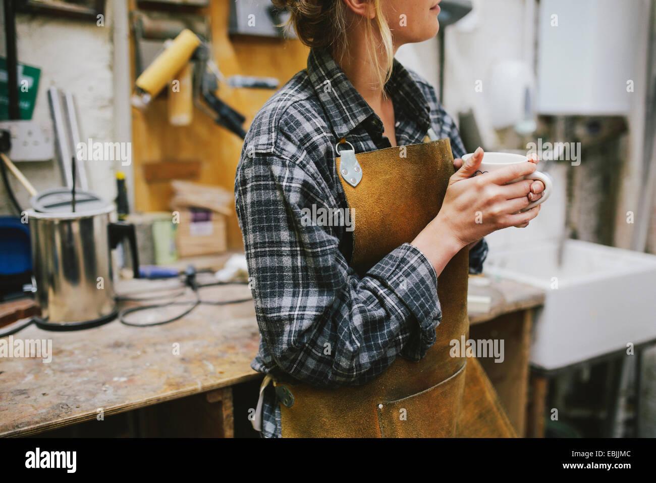 Joven artesana de beber café en taller de órgano de tubos Imagen De Stock