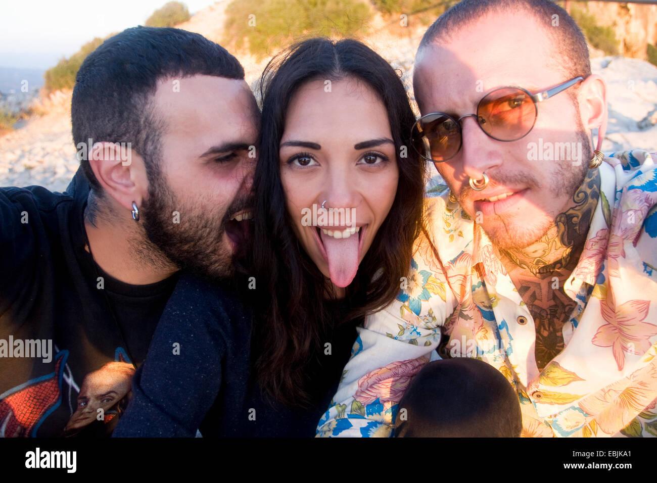 Cerca de tres jóvenes amigos adultos haciendo caras en la costa, Marsella, Francia Foto de stock
