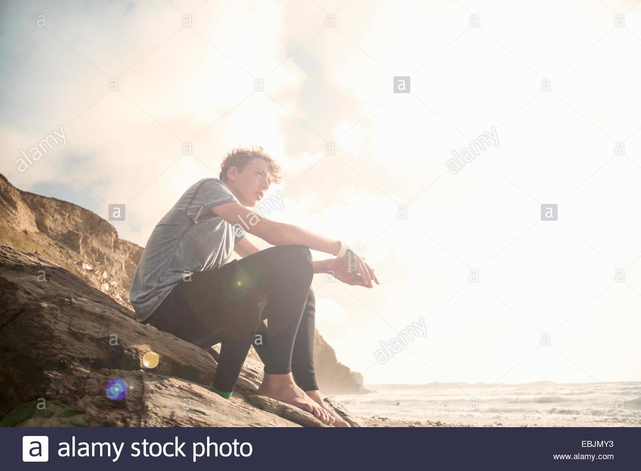 Adolescente sentada sobre las rocas Imagen De Stock